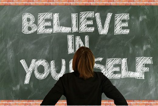 tutor standing in-front of chalk board which says believe in yourself