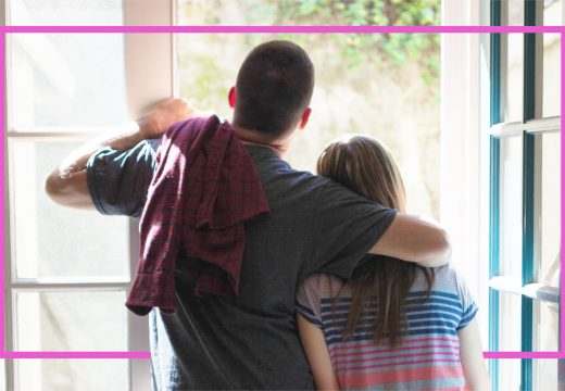 father-with-arm-around-teenage-daughter-by-window